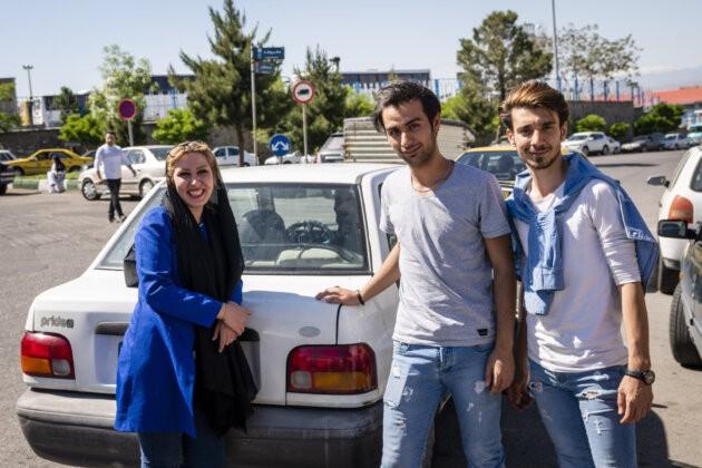 dva moderne obleceni iranci a soudobe odena zena v lehkem hidzabu smeji se