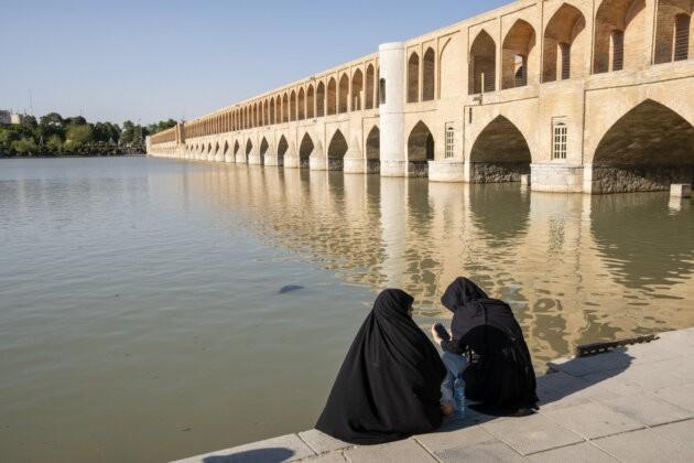 zeny v cadorech na pobrezi reky u mostu v isfahanu