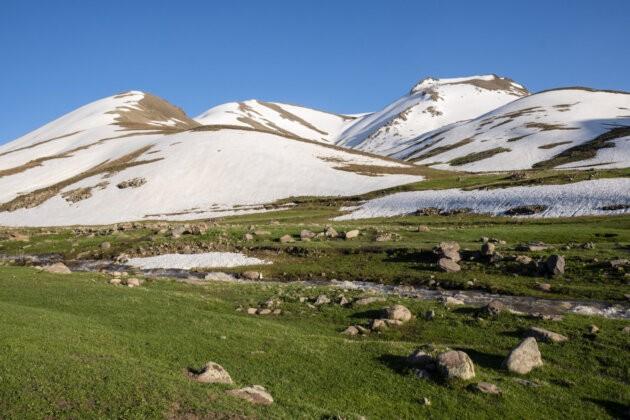 potok skrz zelenou louku se zasnezenymi horami v pozadi