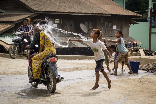 deti polevaji vodou lidi na motorce pri oslave buddhistickeho noveho roku thingyan