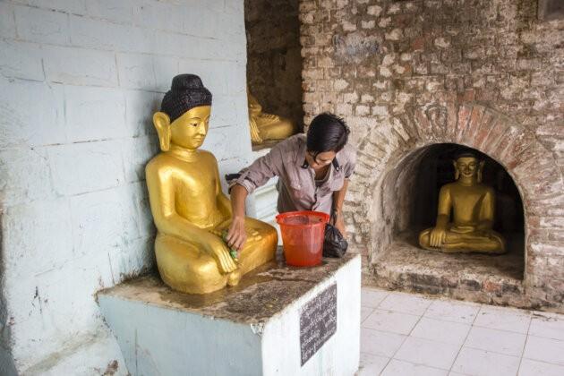barmsky muz omyvajici zlateho buddhu v chramu
