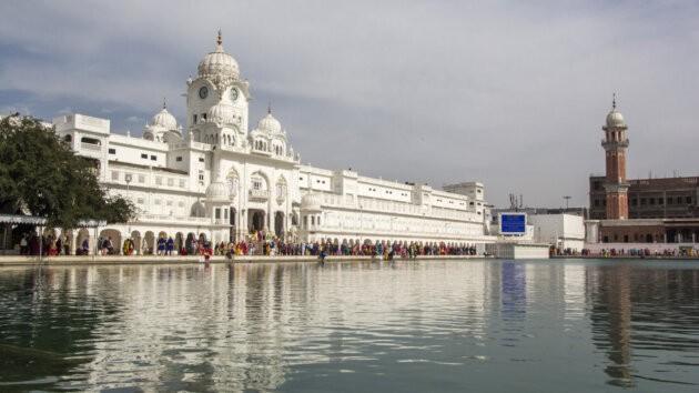 jezero obklopene bilymi budovani zlateho chramu v amritsaru