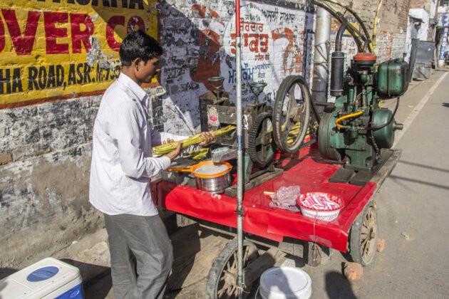 muz lisujici cukrovou trinu na stavu na indicke ulici