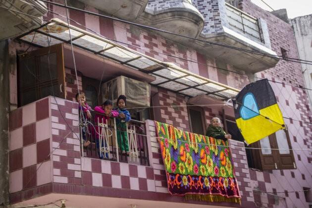 deti poustejici barevného draka z balkonu mezi elektrickymi draty