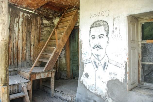 obrazek stalina na zdi a drevene schody