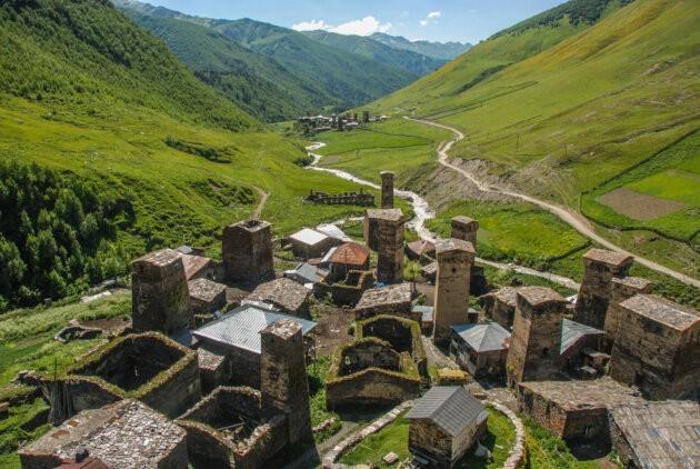 typicka kamenna vesnice v gruzinskych horach zelene udoli v pozadi