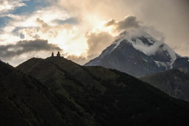 hora kazbek v mracich a kostel nejsvetejsi trojice