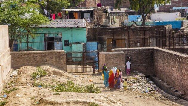 hromada odpadku na ulici pred branou domu v indii a jdouci lide