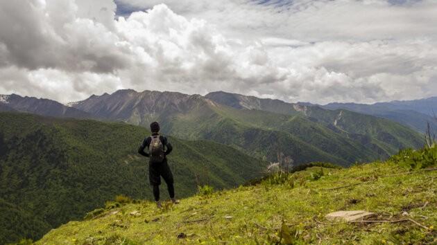 postava nesouci batoh Lowe Alpine Stuff It 22 na kopci