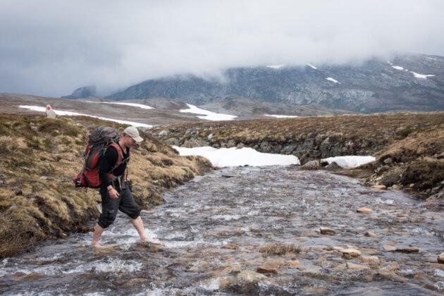 muz brodi ledovou reku mraky a hory norsko