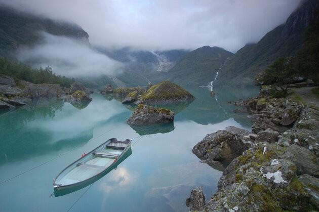 lodka na tyrkysovem jezere mlzna atmosfera