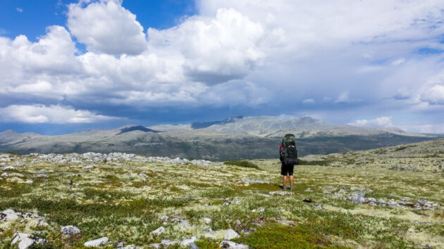 muz s batohem Osprey Aether AG 70 stojici v norske krajine