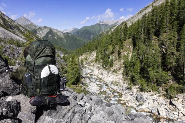 muz s krosnou Osprey Aether AG 70 v horskem udoli